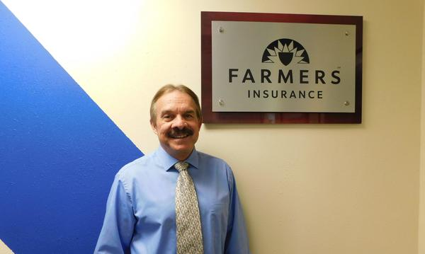 The agent stands in front of a Farmers plaque on the wall