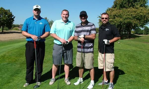 Group photo of four men on a golf course with golf clubs.