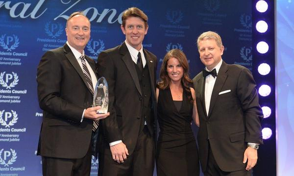 Three well dressed men and a woman posing with an award.