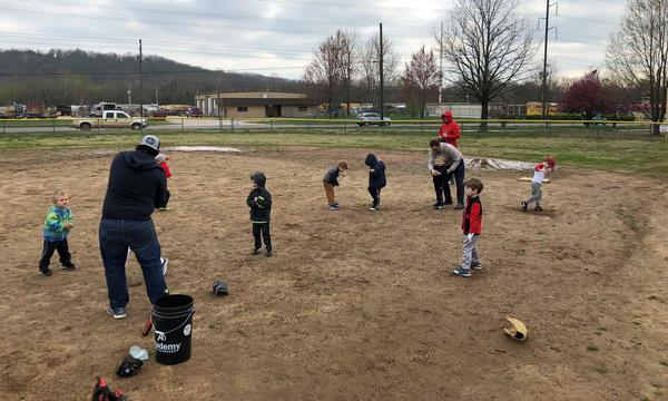 A couple men and a group of children practicing T-Ball.