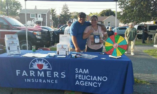 Agent standing with sister behind a Farmers table at an outdoor event