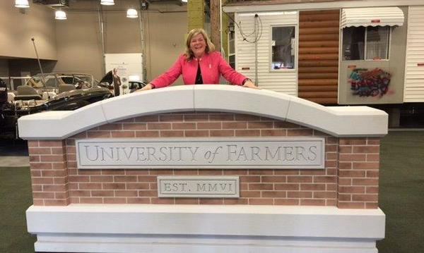 Farmers agent Jennifer standing behind the University of Farmers sign