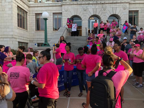 People in pink shirts gathered in front on a building