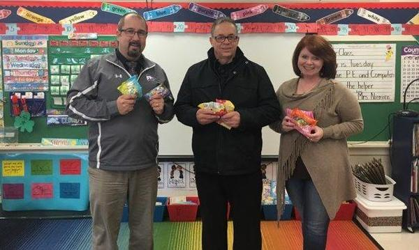 The agent and two teachers posing for a photo with snacks.