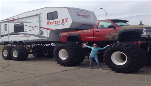 A woman standing with her arms up, in front of a monster truck with an RV cab attached to it.