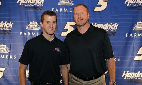 two men in black shirts in front of Farmers Insurance background