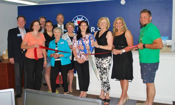 Farmers agency employees cutting a red ribbon for a grand opening ceremony