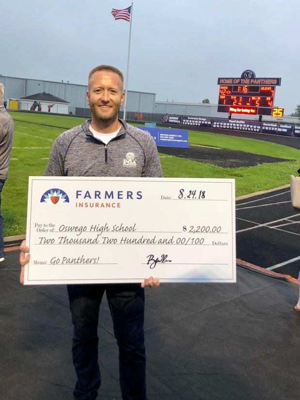 agent holding a giant check for oswego highschool