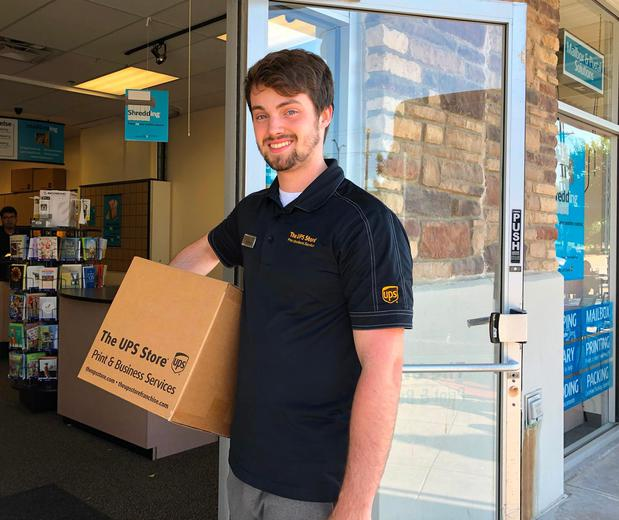 The UPS Store associate carrying a box in front of a The UPS Store