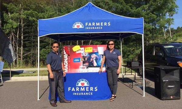Two people pose by a Farmers Insurance booth outside