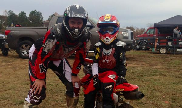 Man and boy stand wearing dirt bike gear, while the boy sits on a dirt bike