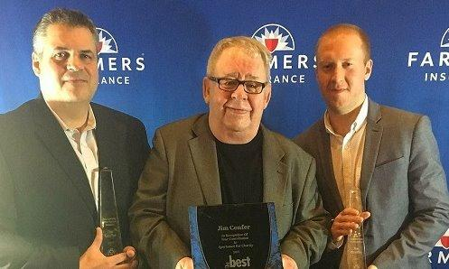 Three men posing for a photo with an award in front of a Farmers Insurance background.