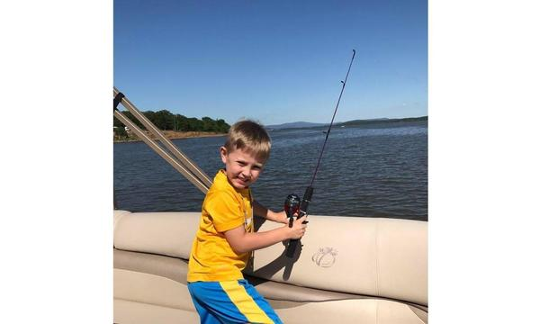 Young boy holding a fishing rod over the side of a boat
