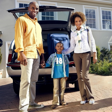Family standing in front of a car.