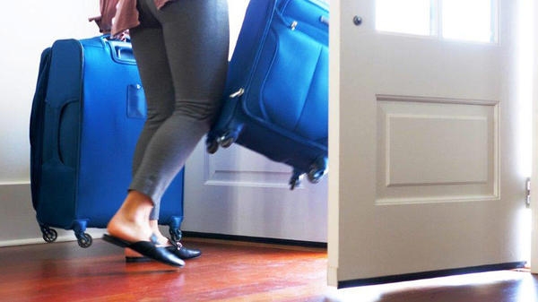 A traveler strides out her front door with 2 rolling luggage cases