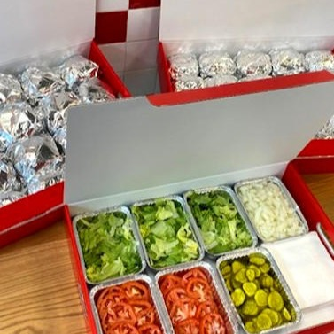 Catering boxes of Five Guys burgers and toppings.