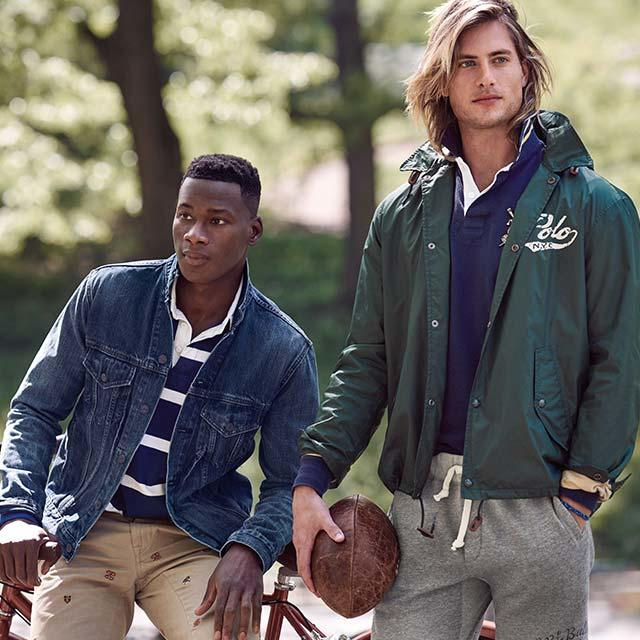 Two men one in a green jacket with a football and the other in navy blue jacket.