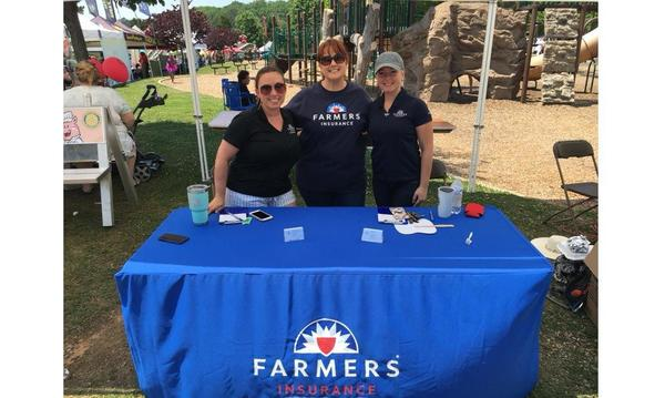 Farmers Insurance staff posing at a Farmers table
