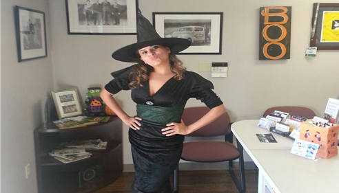 A witch poses with their costume in the office