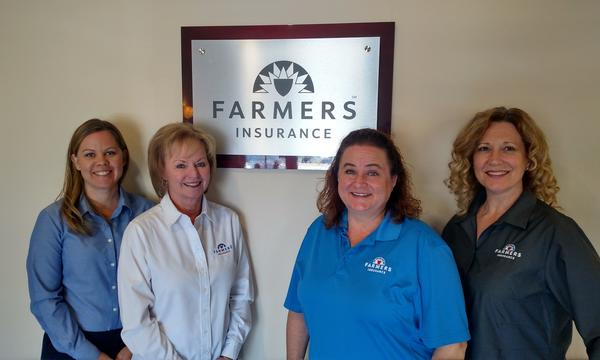 4 female staff members in front of a Farmers sign.