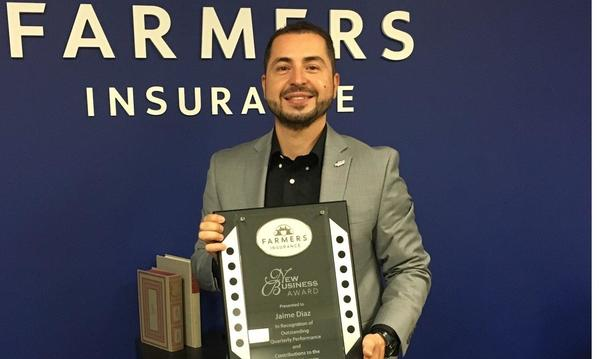 Agent Jaime Diaz standing with an award in front of a blue wall with the Farmers Insurance logo on it.