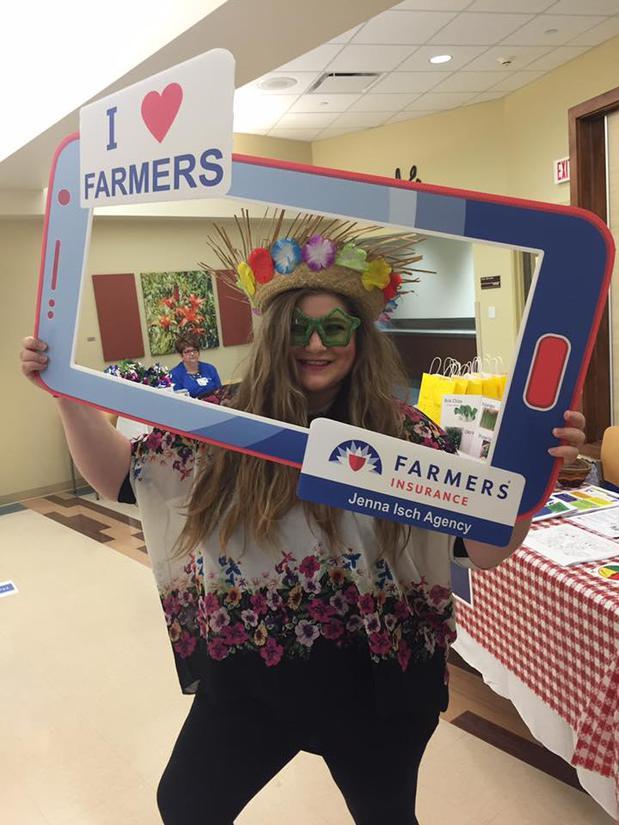 "adult with straw hat posing behind ""I heart farmers"" photo frame"