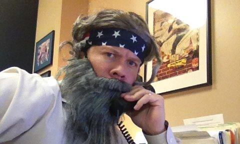 Man wearing fake beard on his telephone
