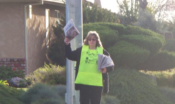 Agent Delia Faria standing on a street corner holding newspapers.