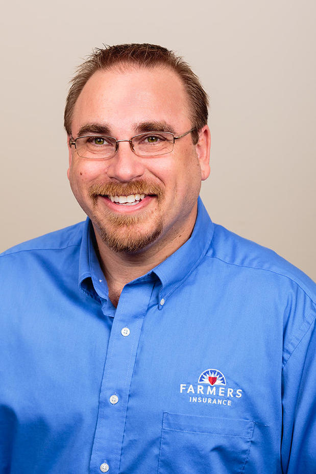 Photo of Staff Member with blue button down with Farmers logo