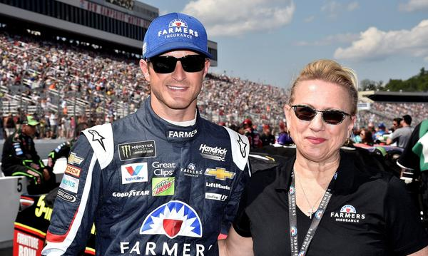 Agent standing with Nascar Driver at a racetrack