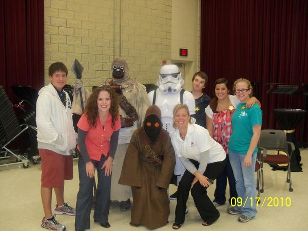 Agent with Star Wars characters and other people smiling.