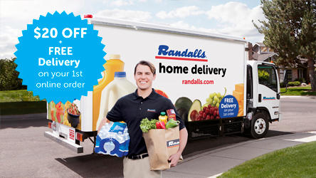 Delivery driver standing in front of Randalls delivery truck holding groceries.