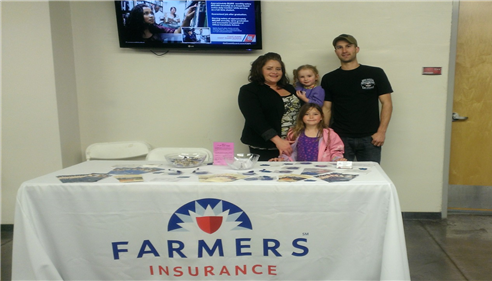 Agent Antoinette Baca standing behind a Farmers Insurance promotional table with her family
