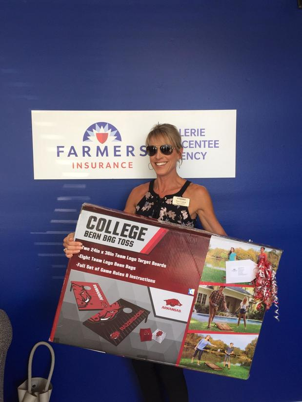 a woman standing with a sign in front of the farmers logo