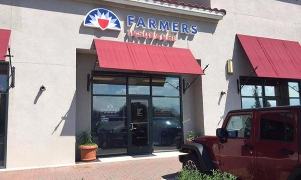 Outside of our office with red awning and Farmers logo