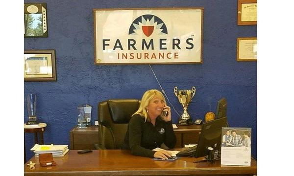 Photo of woman sitting at desk with Farmers club logo in the background.
