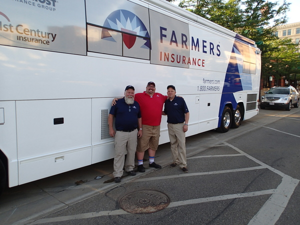 3 people in front of Farmers bus