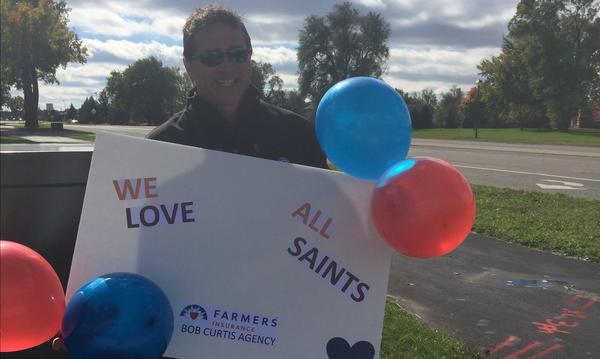 Bob stands outside holding a sign in support of All Saints