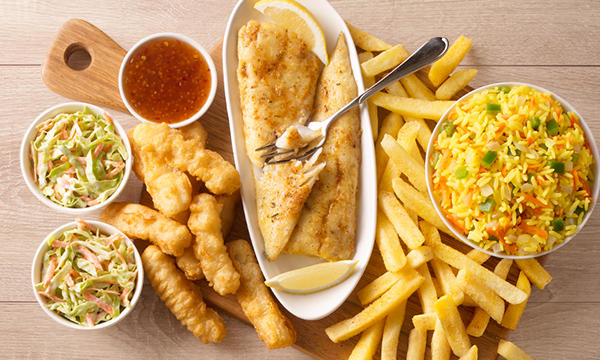 2 grilled fish fillets served with chips, rice, coleslaw, deep-fried calamari strips and a sweet chilli sauce, served on a wooden board.