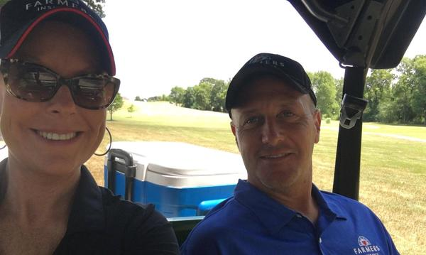 two adults in golf cart