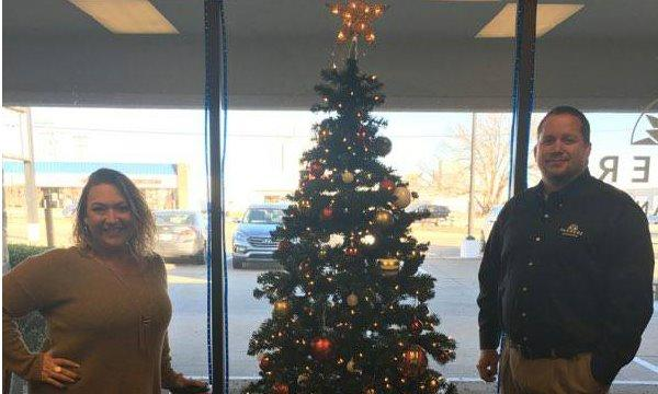 Agent and staff member pose by the office Christmas tree
