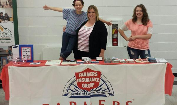 Two women and a child standing behind a Farmers booth at an event