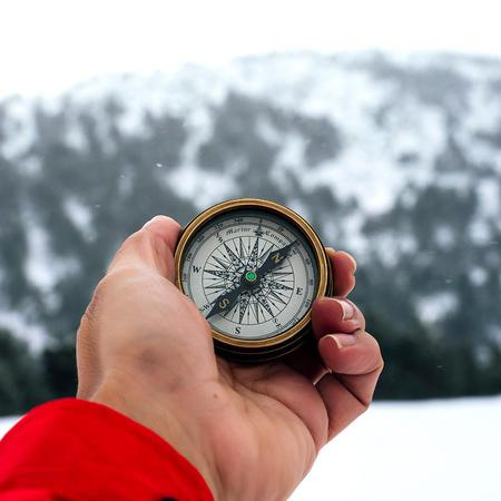 A hand holds a compass in the snowy mountains