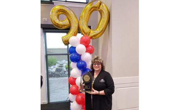 Agent Delia Faria with an award, standing in front of balloons.