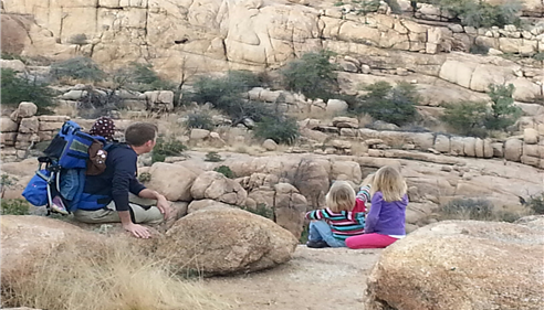 A man and two little girls sit down for a rest during a hike