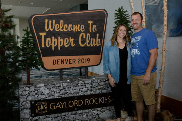 Agent and wife next to Topper Club sign