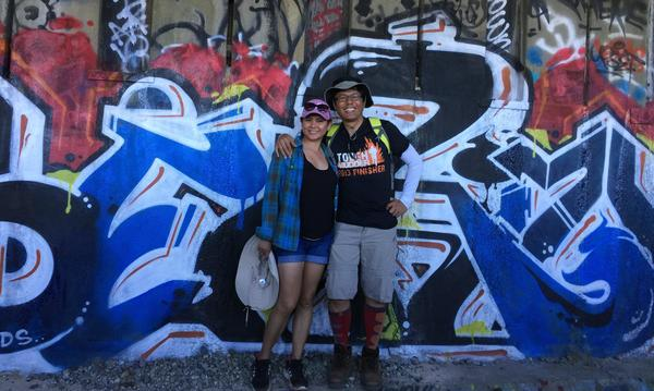 Two people standing in front of a graffiti-covered wall looking at the camera and smiling