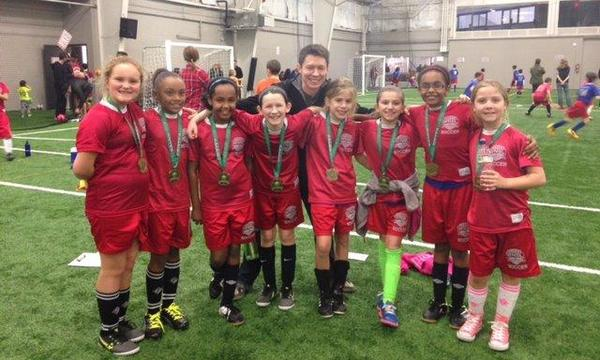 Agent Jason Egly standing on a field with a youth girls soccer team.