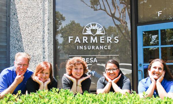Five staff members posing over bushes by Farmers logo