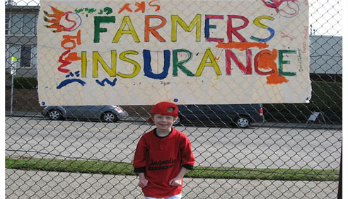 A young baseball player stands in front of a hand-made sign for Farmers Insurance